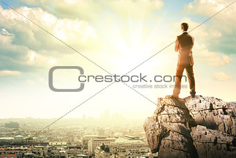 Young businessman standing on edge of rock