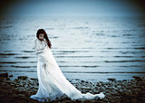 Beautiful sad girl in white dress standing on sea coast