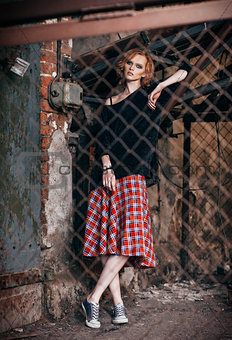 Portrait of beautiful grunge girl in plaid skirt and sweater standing behind metallic lattice