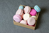 Colorful macaron in a box on the background of gray fabric