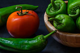 tomato and chili pepper on a dark background