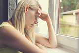 tired, depressed woman sitting by the window