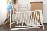young pregnant woman assembling bed for expectant baby