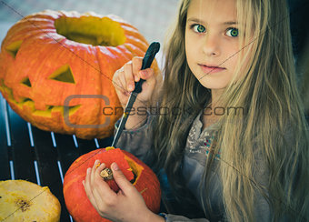 Beautiful girl with green eyes cut a pumpkin for Halloween.