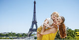 mother and child tourists embracing in front of Eiffel tower