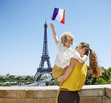 mother and child travellers rising flag in Paris, France