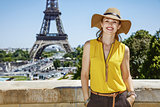 smiling woman in bright blouse in front of Eiffel tower, Paris