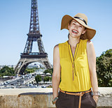 happy young woman in bright blouse against Eiffel tower in Paris