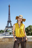 smiling woman in bright blouse in front of Eiffel tower in Paris