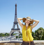 relaxed woman in bright blouse in front of Eiffel tower in Paris