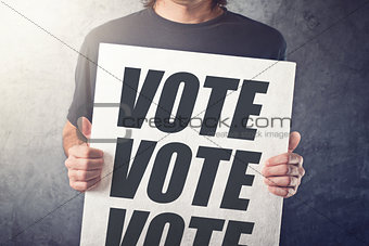 Man holding poster with Vote label
