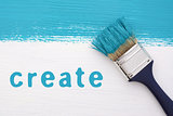 Stripe of turquoise paint, paintbrush and the word CREATE