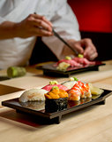 Assorted Sushi with Chef as background