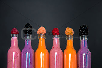 Six bottles with smoothies and raspberry, red, yellow, blackberry on black background. Milk shake in glass jar berries. diet or vegan food concept, fresh vitamin.