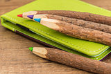 colored wooden pencils and green brown leather workbook