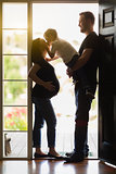 Young Son Kissing Pregnant Mom with Daddy in Doorway