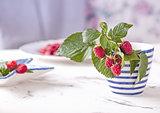 Fresh branch of raspberries in blue white stripped mug on table