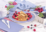 pancakes with raspberry, currant on blue stripped plate with textile, close-up white marble background