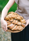 Woman holds in hand a wooden tray with the cut bread