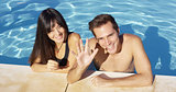 Smiling couple standing in clear pool wave