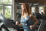 Young strong girl running on treadmill in gym