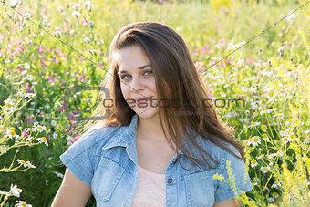 Portrait of girl of 16 years in flower meadow