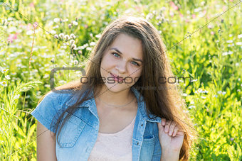 15 year girl with long brown hair on summer glade
