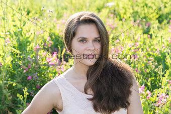 Portrait of girl of 16 years in flower meadow