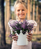 Beautiful girl in the forest holding in a vase with heather.