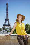 relaxed woman in bright blouse against Eiffel tower in Paris