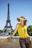 young woman in bright blouse in front of Eiffel tower in Paris