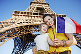 mother and child tourists showing flag near Eiffel tower, Paris