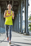 sportswoman running on Pont de Bir-Hakeim bridge in Paris
