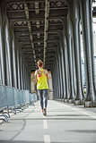 active woman running on Pont de Bir-Hakeim bridge in Paris