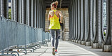 sportswoman jogging on Pont de Bir-Hakeim bridge in Paris