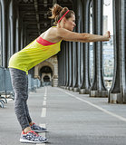 woman jogger stretching on Pont de Bir-Hakeim bridge in Paris