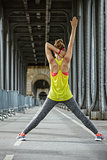 healthy woman stretching on Pont de Bir-Hakeim bridge in Paris