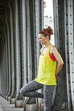 healthy woman looking into distance on Pont de Bir-Hakeim bridge