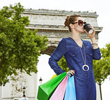 woman with shopping bags drinking coffee on Champ Elysses, Paris