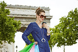 Young woman with shopping bags near Arc de Triomphe in Paris