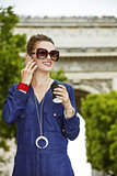 woman speaking on a smartphone while drinking coffee in Paris