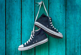 pair of blue men's sports sneakers hanging from a nail on the wa