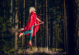 Modern witch blond in jeans and red cape flying on a broom through the forest. Levitation. Halloween holiday.