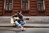 Man plays on guitar at the street