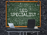 SEO Specialist on Chalkboard with Doodle Icons.