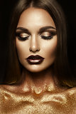 Beautiful girl with gold glitter on her face