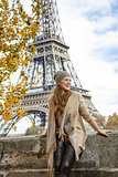 young elegant woman on embankment in Paris exploring attractions