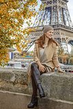 woman looking into distance while sitting on parapet in Paris