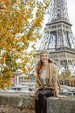 elegant woman sitting on parapet on embankment near Eiffel tower