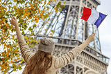 elegant woman on embankment in Paris, France rising flag